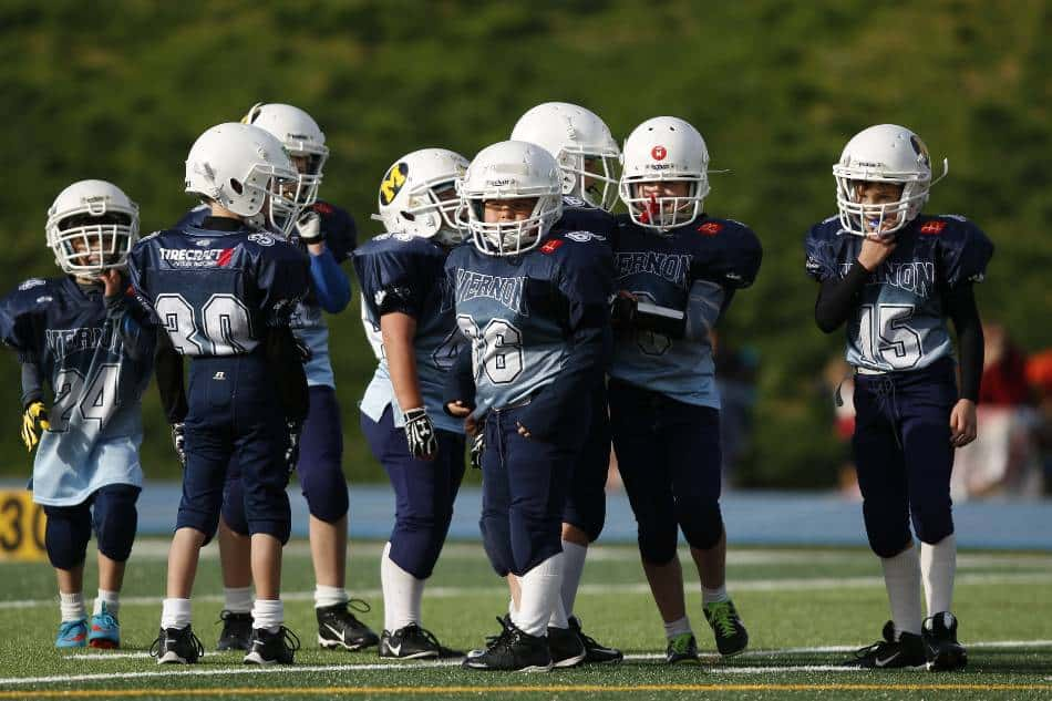 Youth football players look to the sidelines before running a play.
