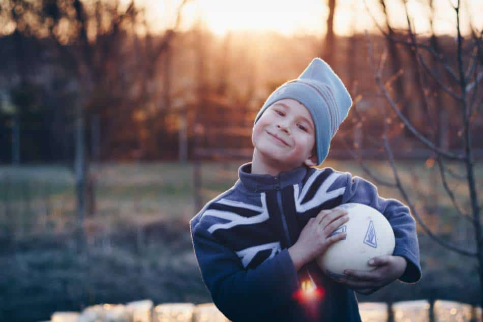 Smiling boy holds a small soccer ball.