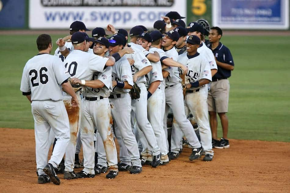 Baseball team celebrates after winning a game.