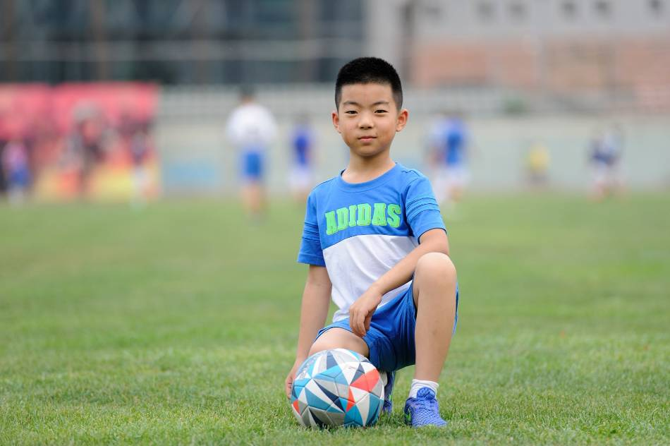 Young boy posing for the camera with a soccer ball.