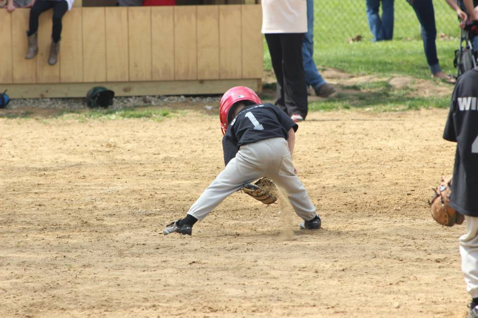 Young baseball player with a helmet on playing in the dirt with his glove.