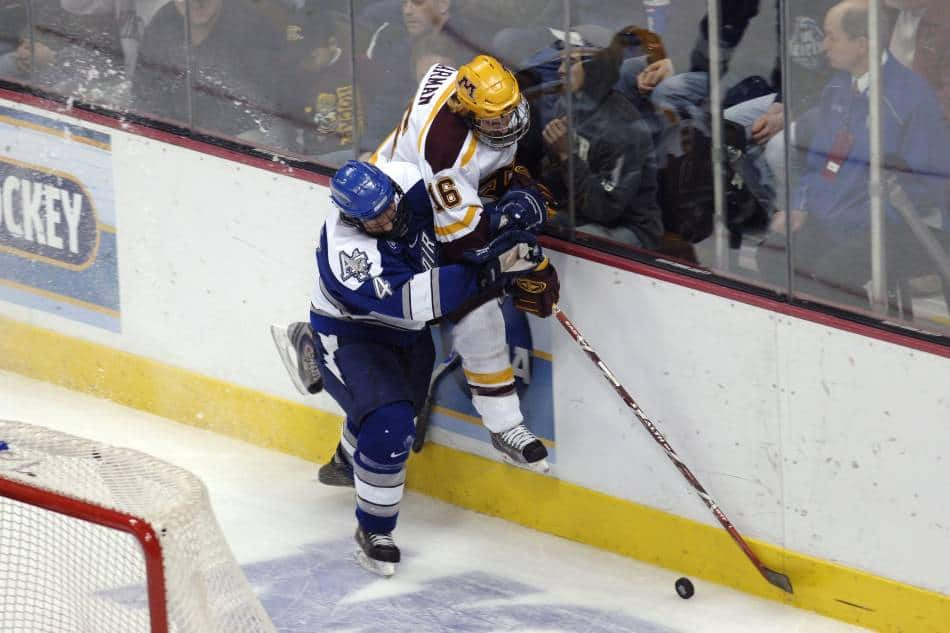 College hockey players battle for puck along the boards.