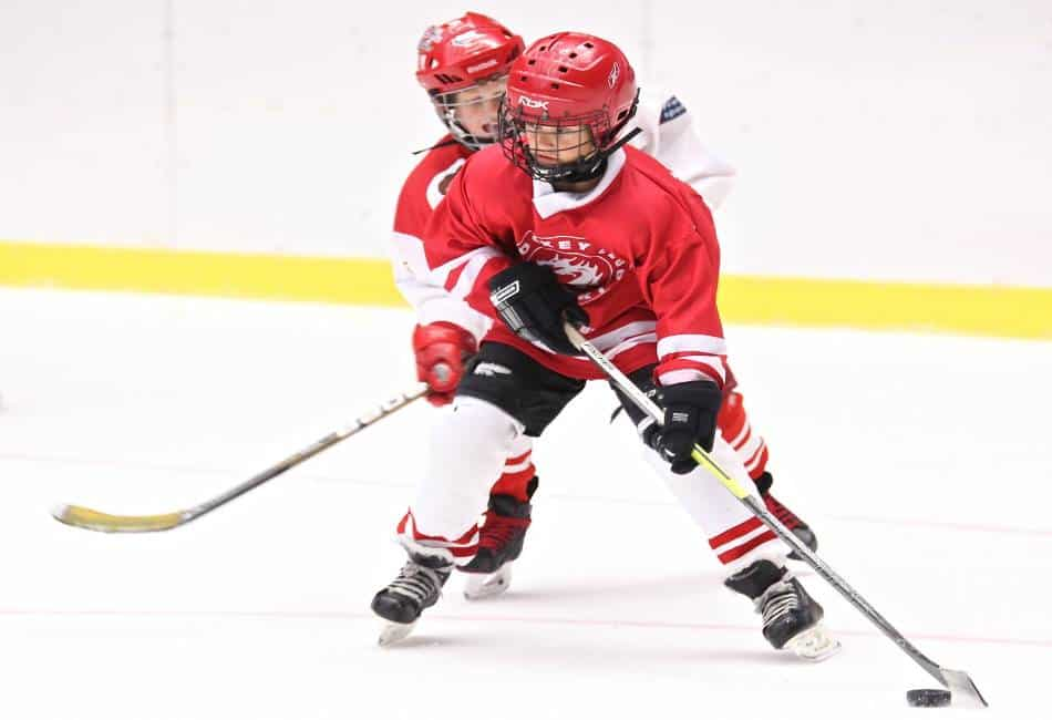 Youth hockey player protects the puck from the other team.