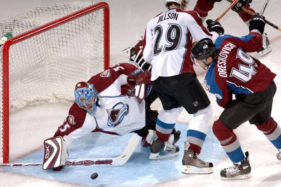 Hockey goalie dives to block the hockey puck.