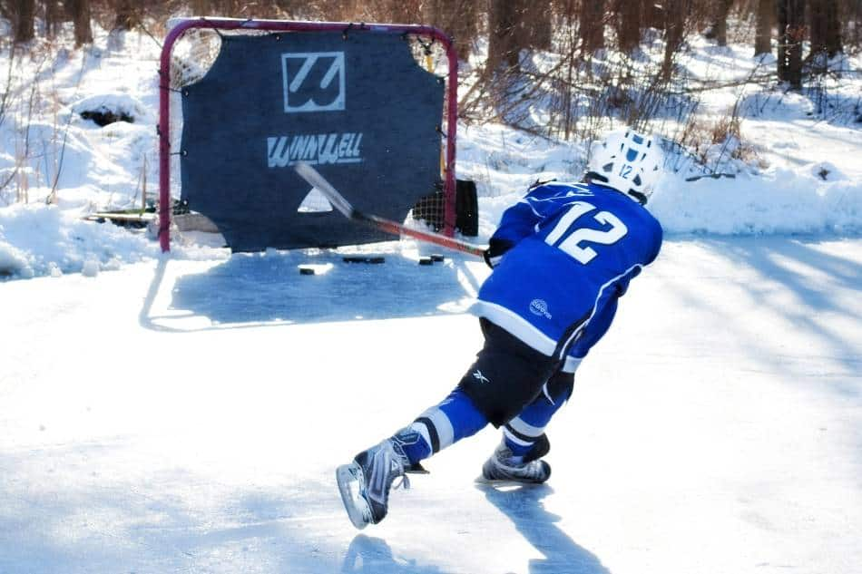 Youth hockey player shoots on net outdoors.