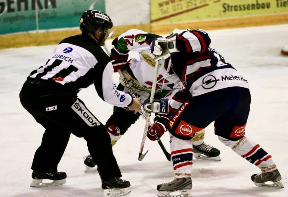 Two hockey players line up for a faceoff.