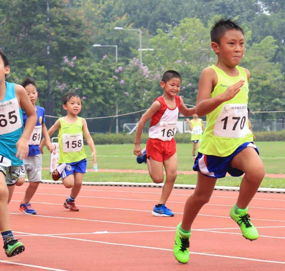 Boys with different numbers racing on a track.