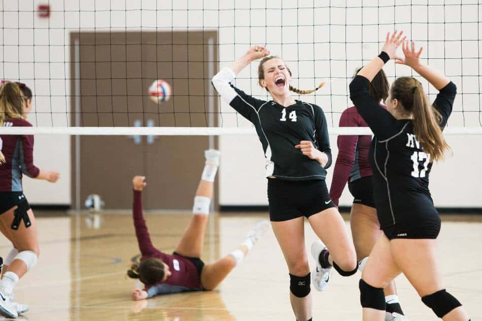 Girl's volleyball team celebrates scoring a point.