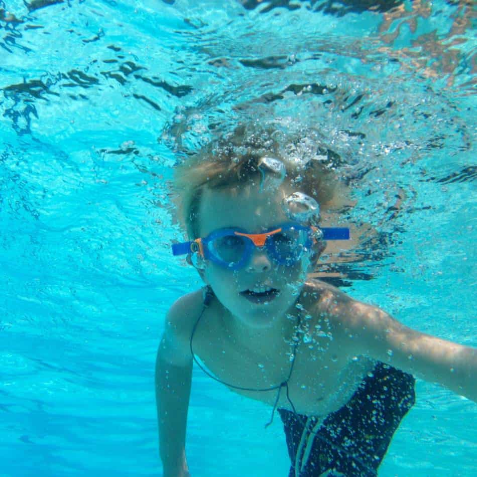 Boy with blue and orange goggles swims underwater.