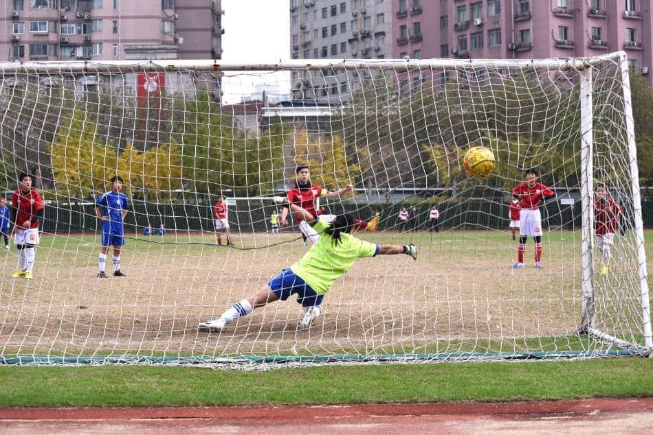 Soccer player shoots ball past goalie.