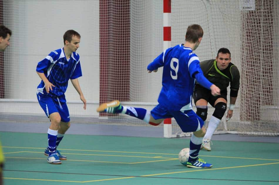 Soccer goalie looks to block a player's shot in indoor soccer.