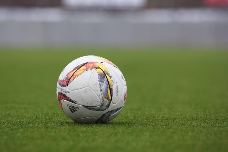 Soccer ball motionless on soccer field.