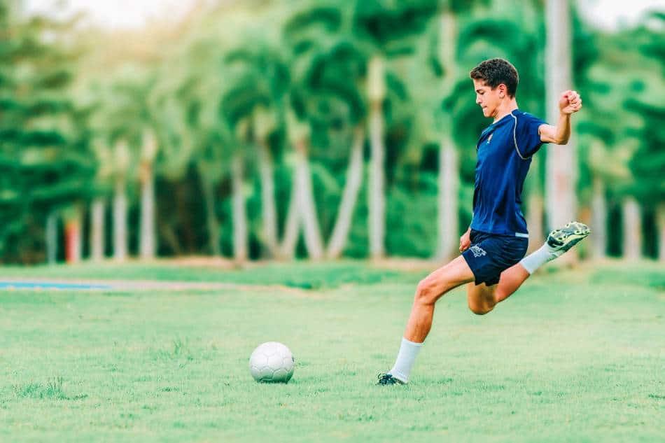 Male soccer player taking a goal kick.