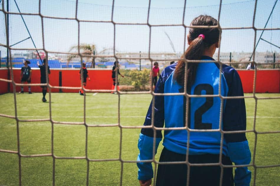 Female soccer goalie looks on as her team tries to score.