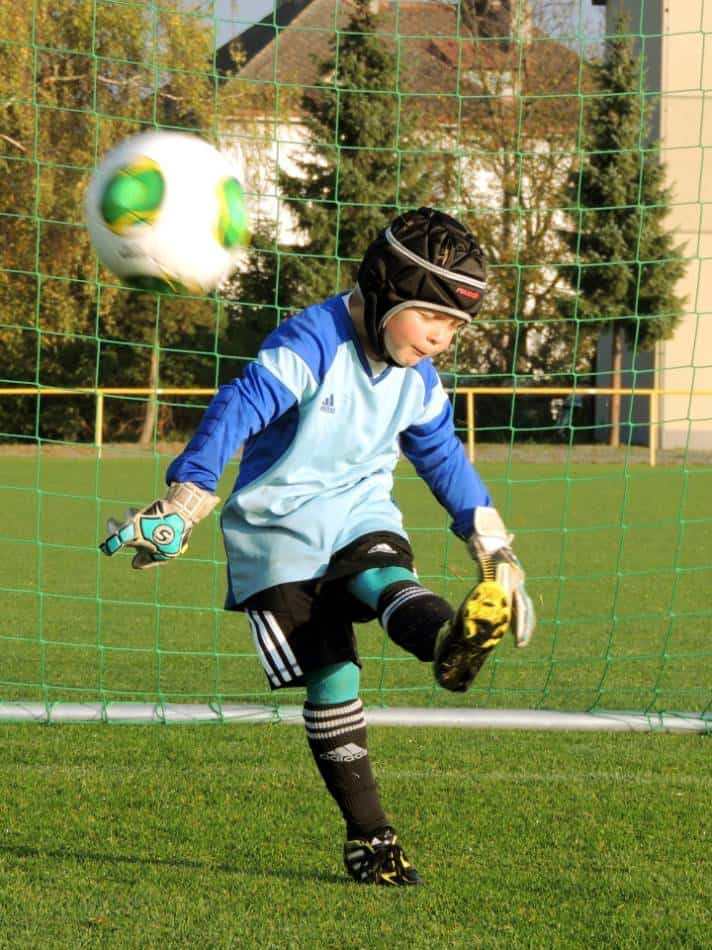 Youth soccer goalie closes his eyes while punting the ball.