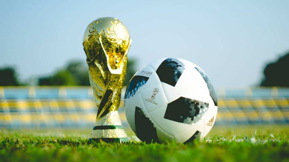 Soccer ball next to replica World Cup trophy.