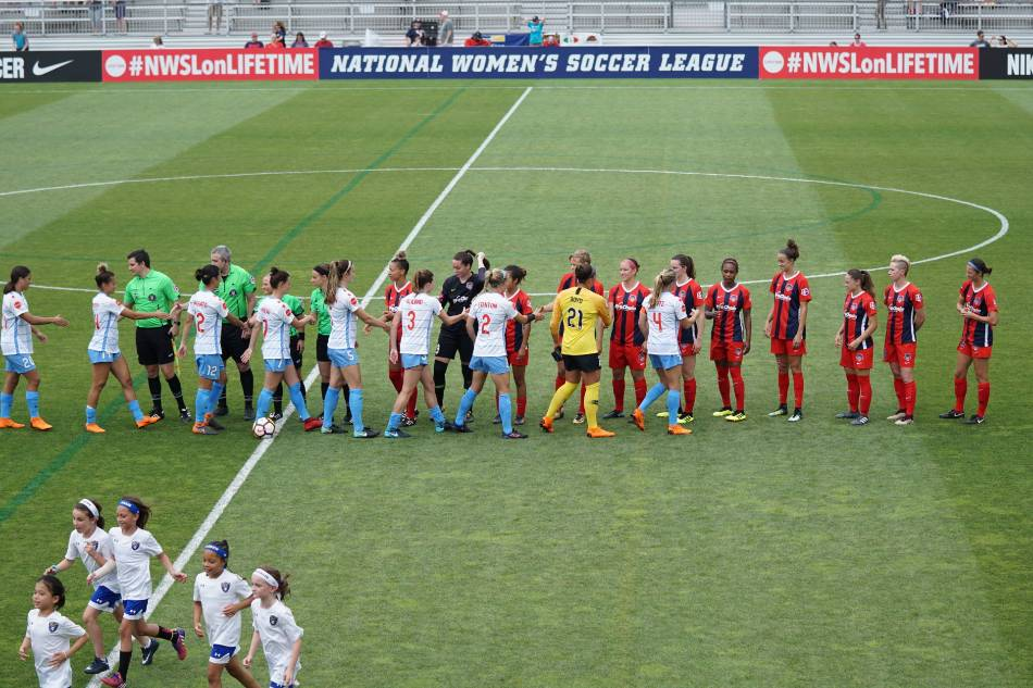 Women's soccer teams shaking hands before the game starts.