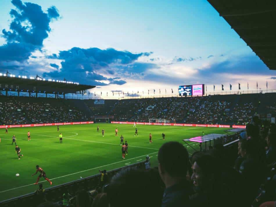Soccer stadium full of fans watches games.