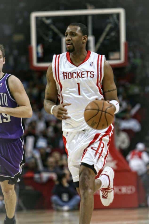 Professional basketball player dribbles ball toward basket.