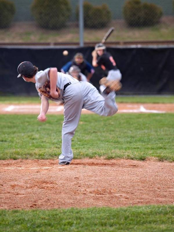 Youth pitcher throws the ball during at-bat.