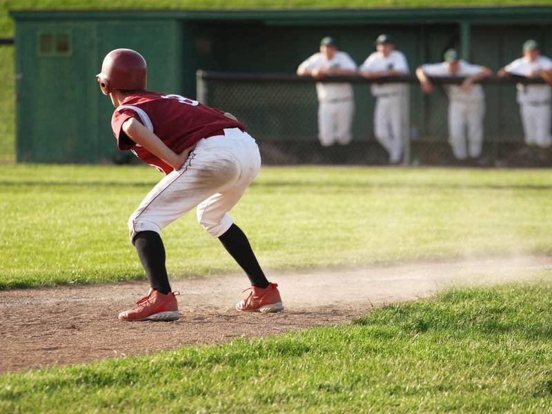 Baseball player takes a lead off third base.