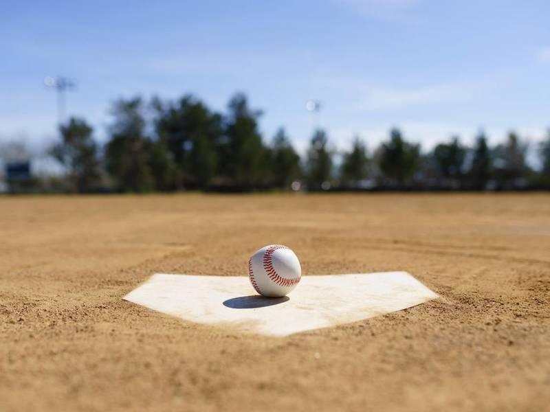 Baseball sitting on home plate.