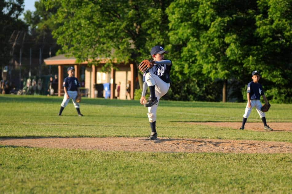 Youth baseball player on the Yankees throwing a pitch home as first base and right field look on.