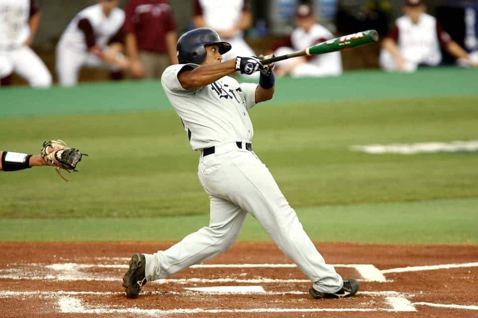 College baseball player swings at a pitch.
