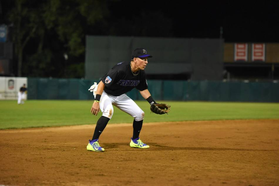 Baseball player gets in the ready position on the left side of the infield.