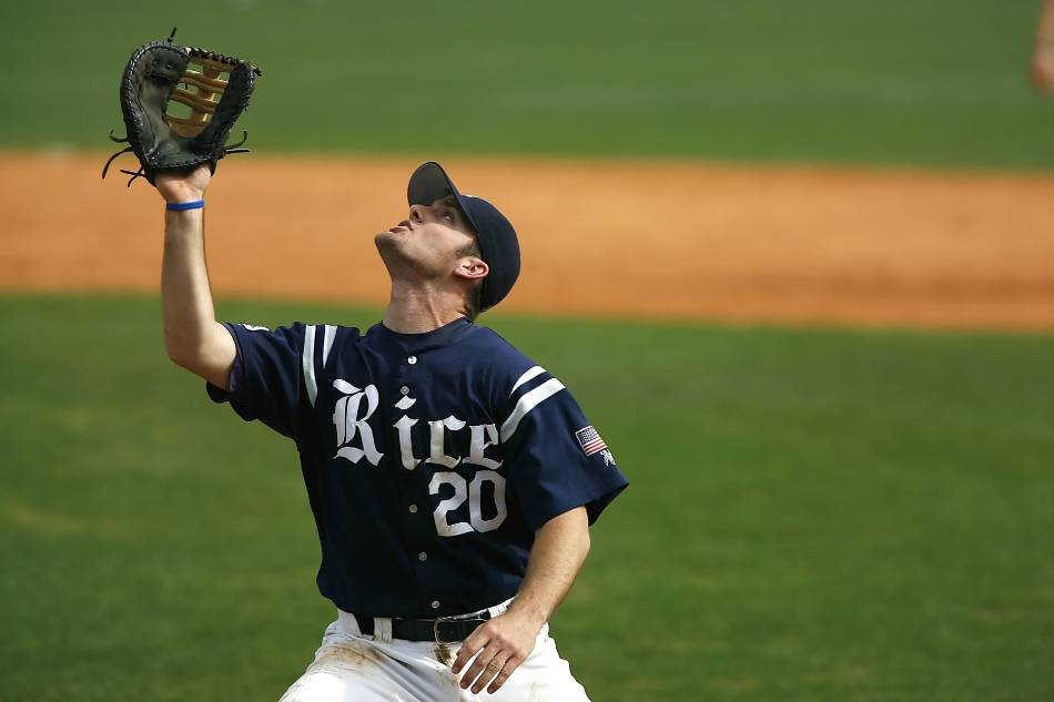 Left-handed college baseball player in blue and white prepares to catch an infield pop-up.