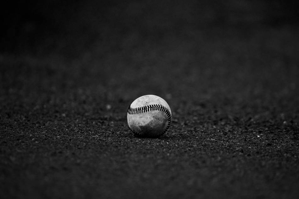 Black and white photo of a baseball lying in the dirt.
