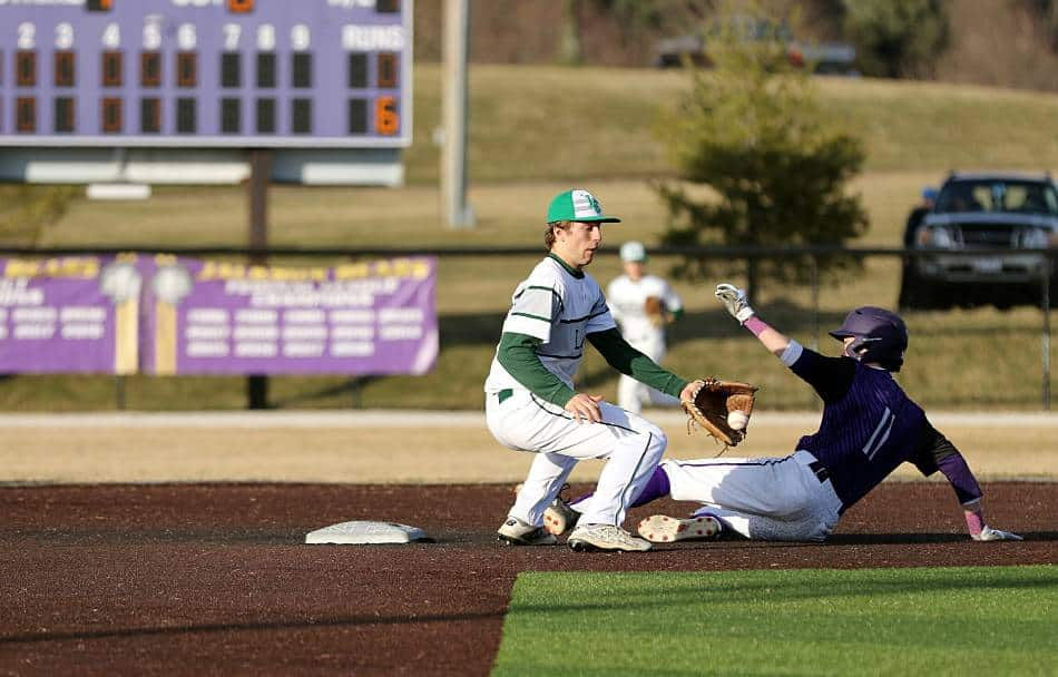 Baseball player in white and green prepares to tagout runner in purple and white.