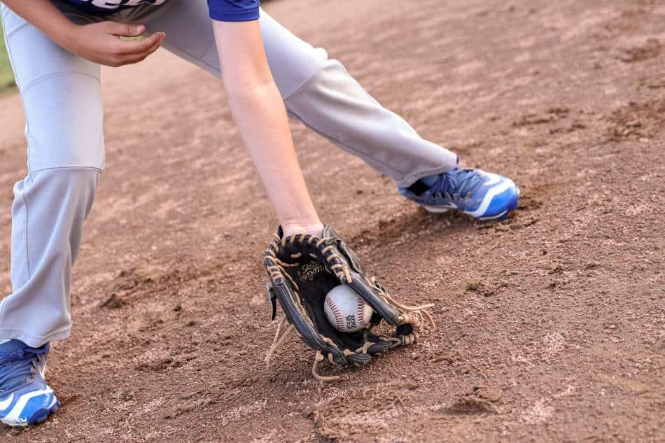 Youth baseball player fields a groundball.