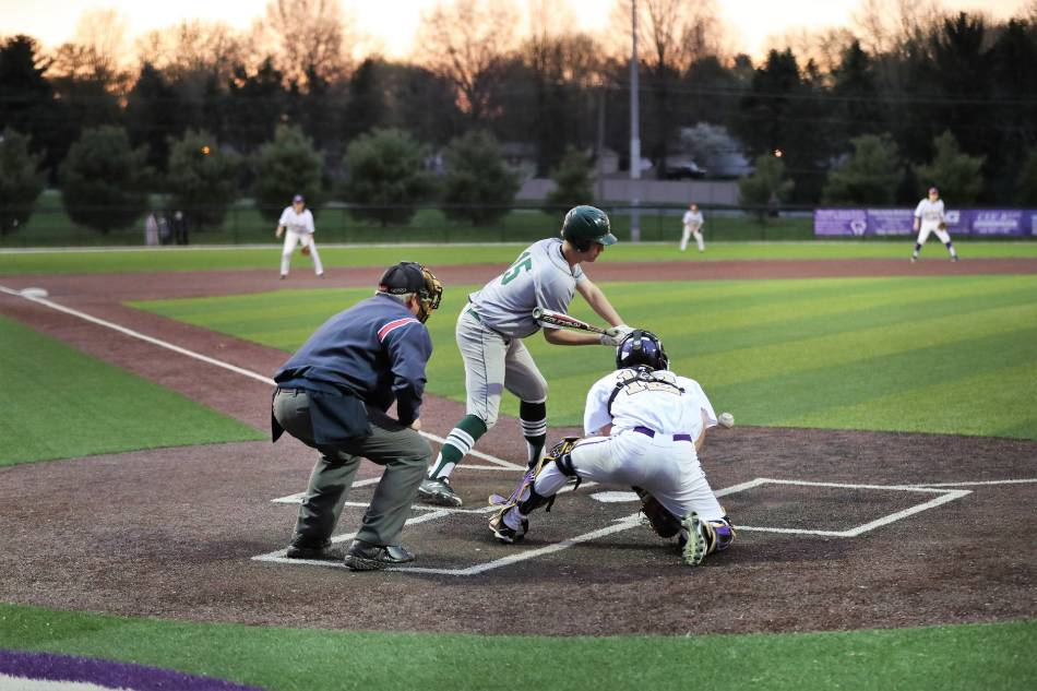 College baseball player in grey and green checks his swing, while catcher blocks the pitch.