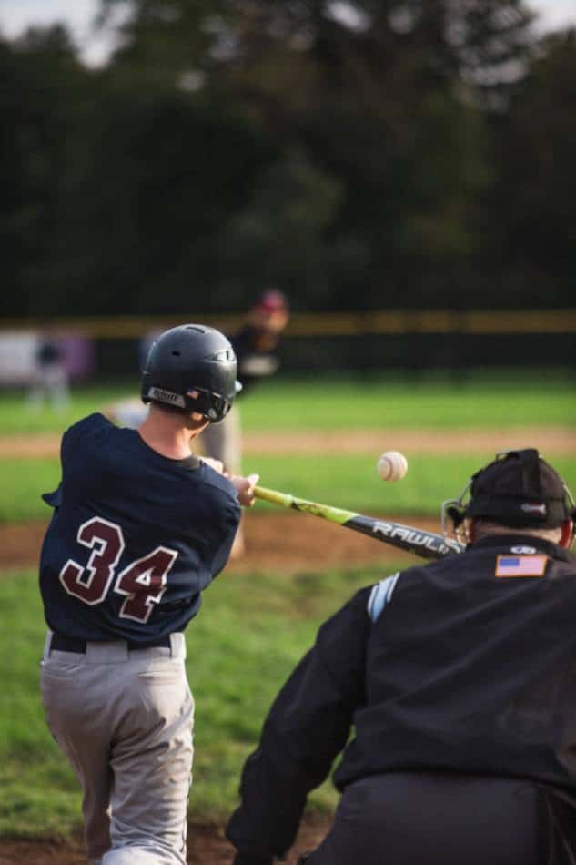 High school baseball player squares up a pitch.