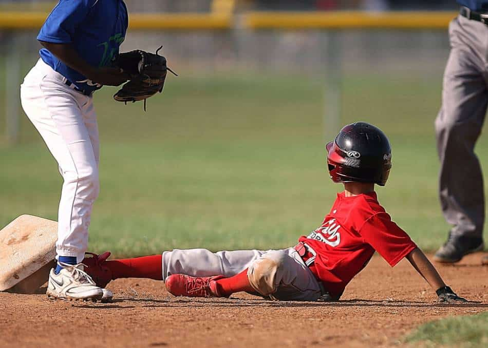 Youth baseball player in red knocks second base off by sliding into it.