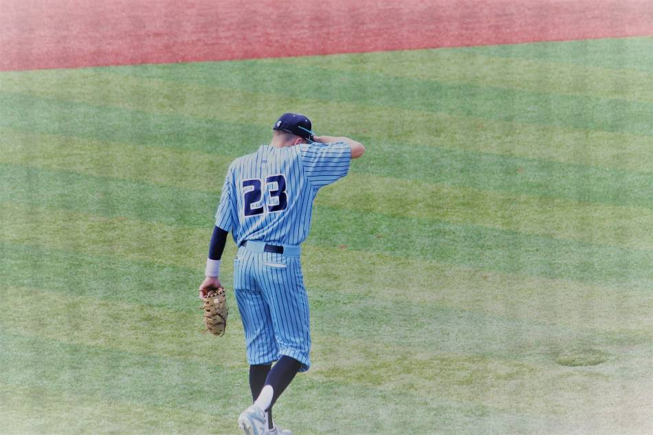 Baseball player in pin stripes takes the field.