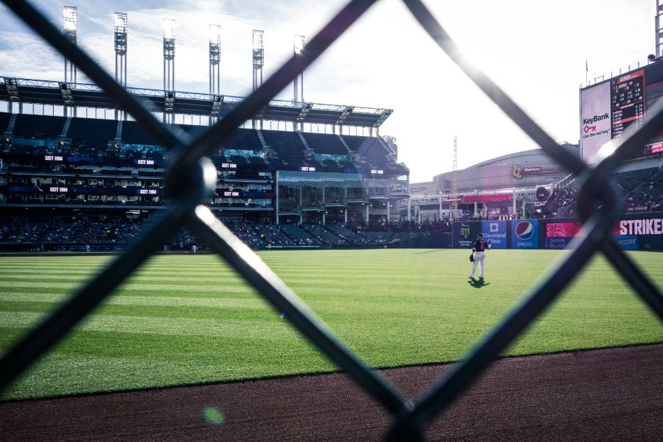 View from the outfield of a baseball game through a chain-link fence.