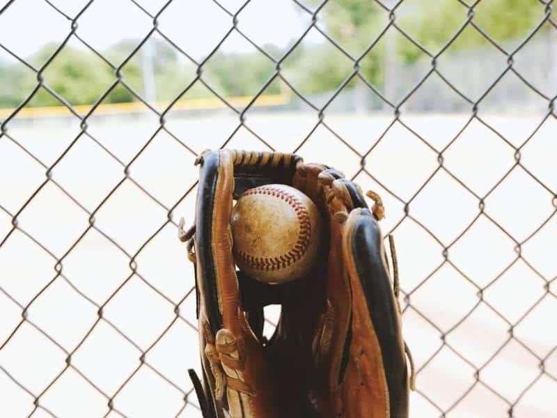 Glove against fence holds baseball.