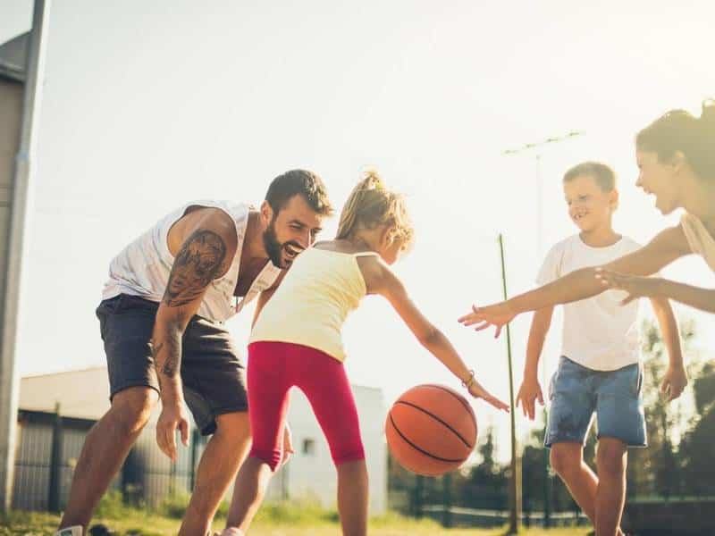 Young girl dribbling basketball with family.