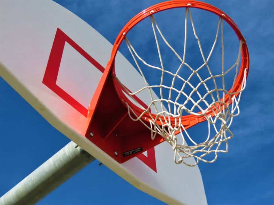 View of a basketball hoop at the park from beneath the rim on a sunny day.