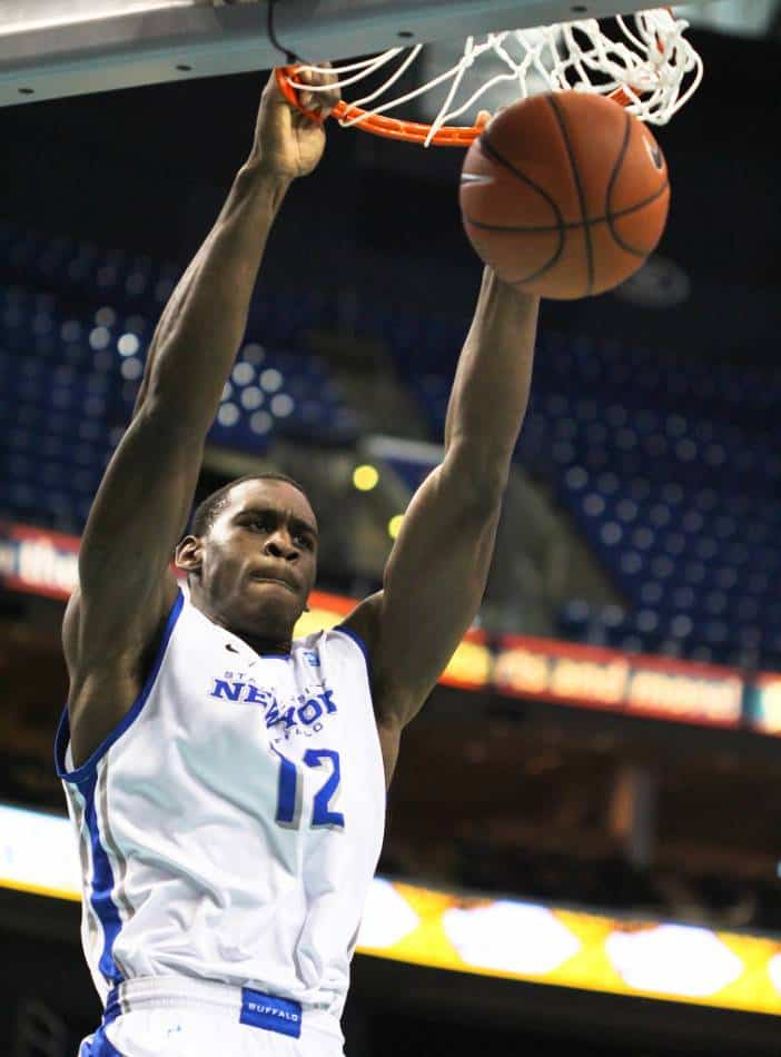 Basketball player in white and blue dunks the ball.