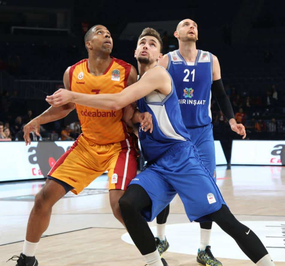 Basketball player in blue and white defenders against a player in orange and red.