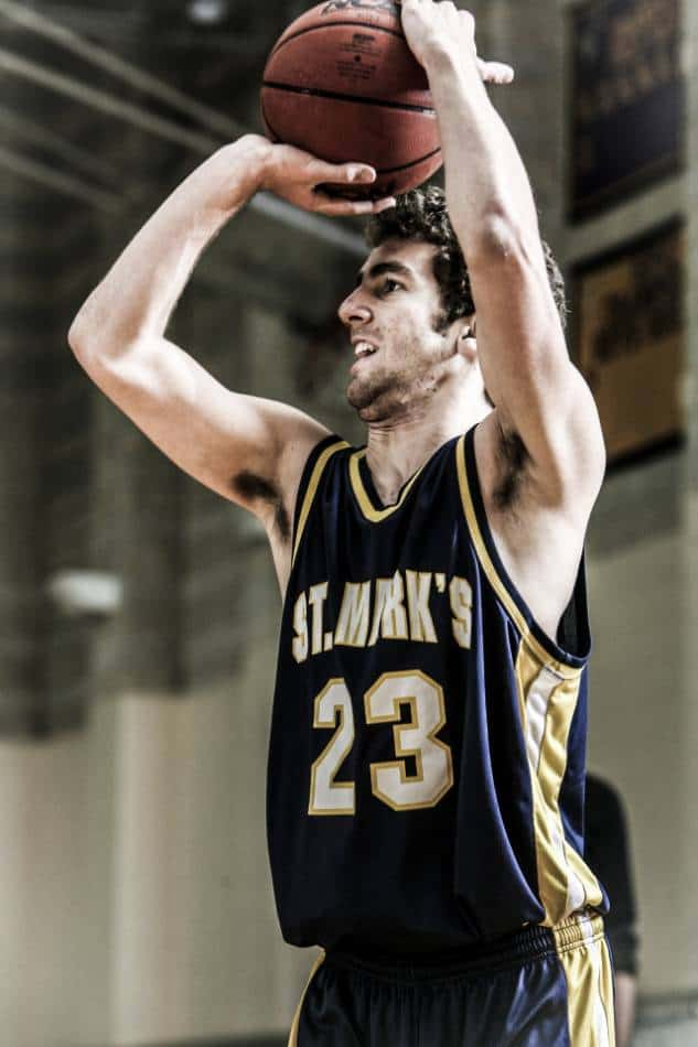 College basketball player in blue and gold takes a jump shot.