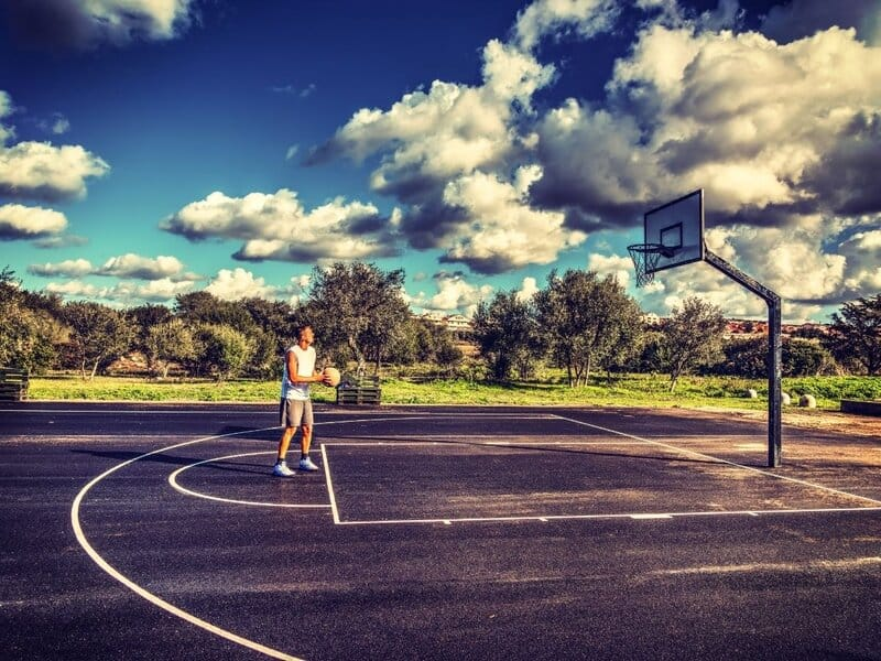 Man in white tank top shooting free throws at the park.
