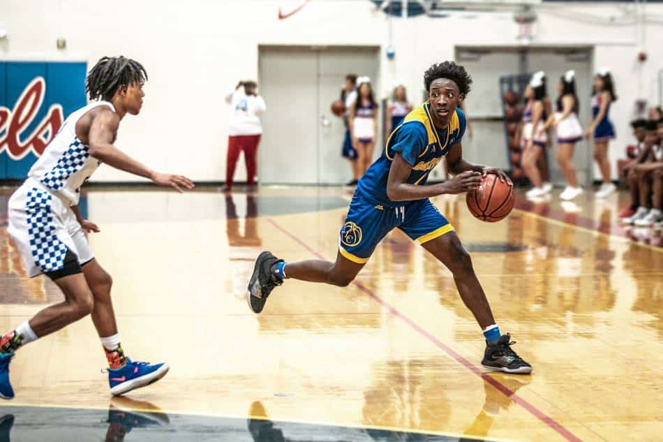 Basketball player in blue and gold dribbles the ball to avoid traveling.