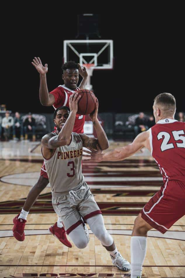 College basketball player in silver and red drives to the basket against players in red.