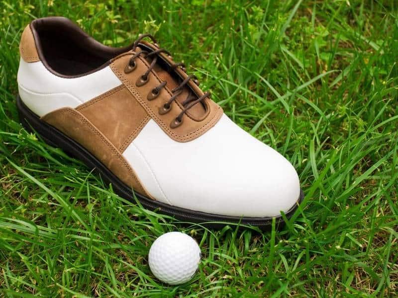 Golf shoe next to golf ball in grass.