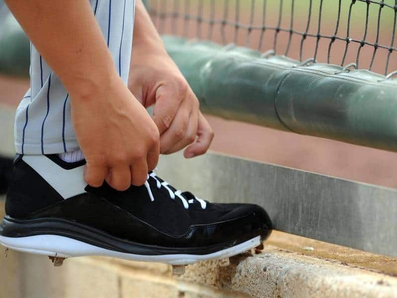 Baseball player tying his cleats.