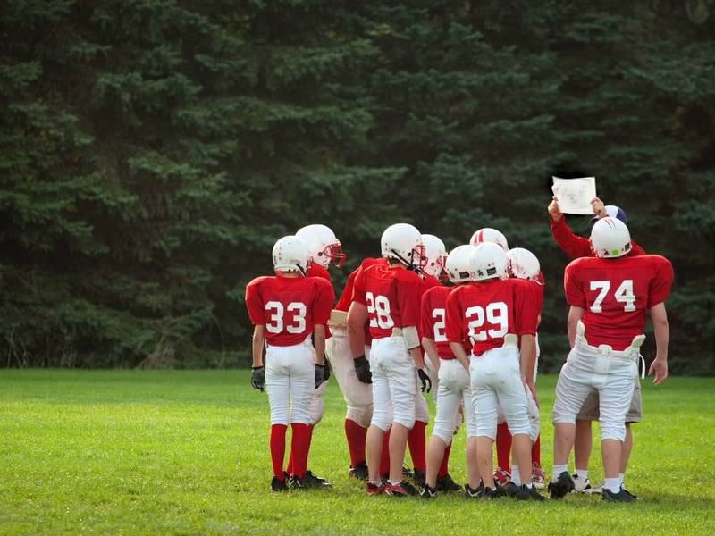 Youth football coach shows his team a play.